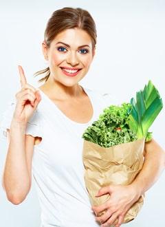 Giovane Donna In Possesso Di Un Sacco Di Carta Con Le Verdure